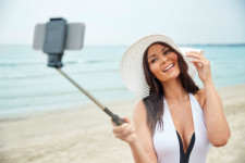 woman using selfie stick on the beach - SMALL